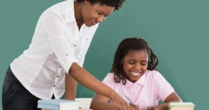 African American woman tutoring an African America young girl.